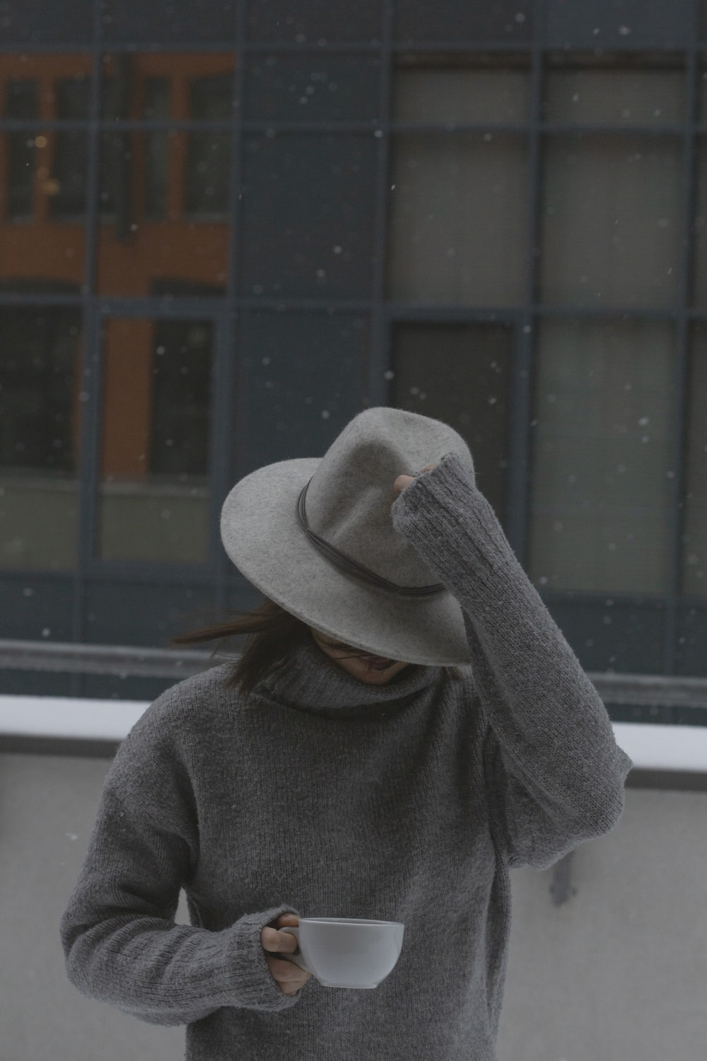 person in gray sweater wearing gray knit cap