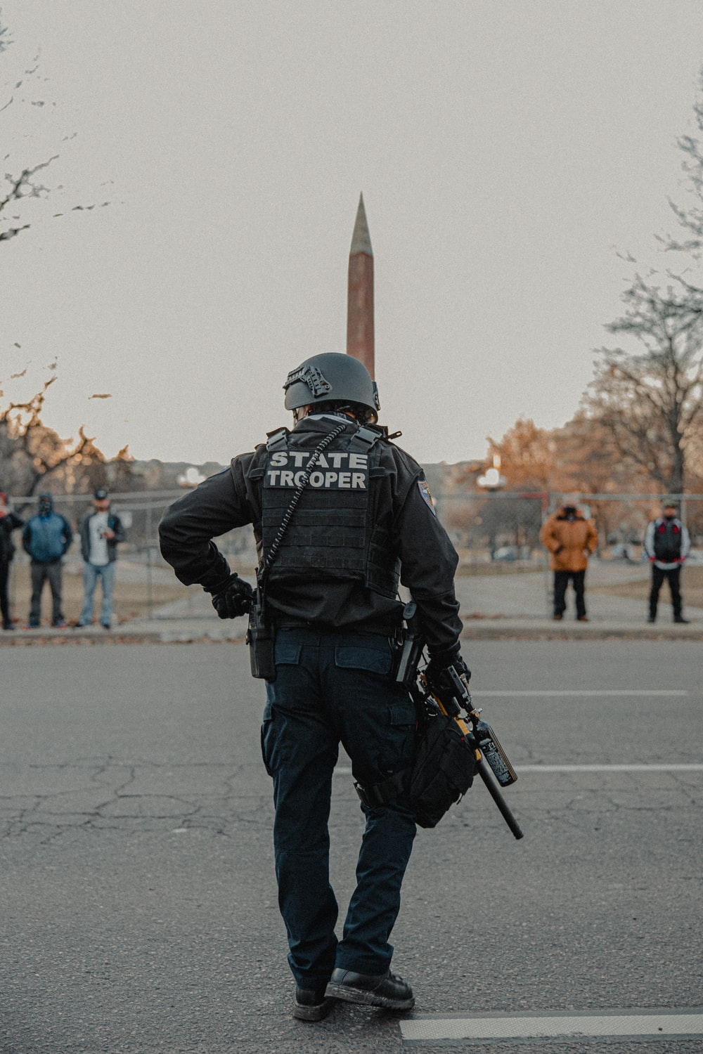 man in black jacket and pants holding black rifle