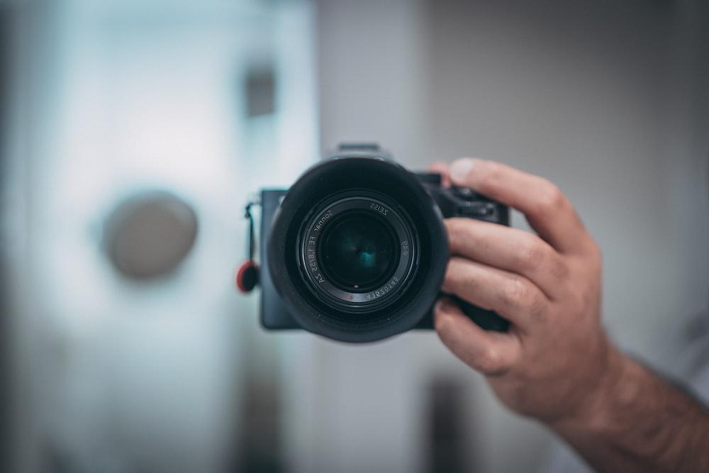 黒のデジタル一眼レフカメラを持っている人