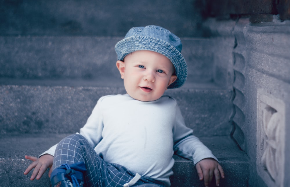 baby in white long sleeve shirt and blue and white plaid pants sitting on gray concrete