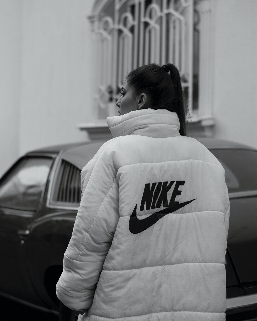woman in white and black adidas hoodie standing near black car