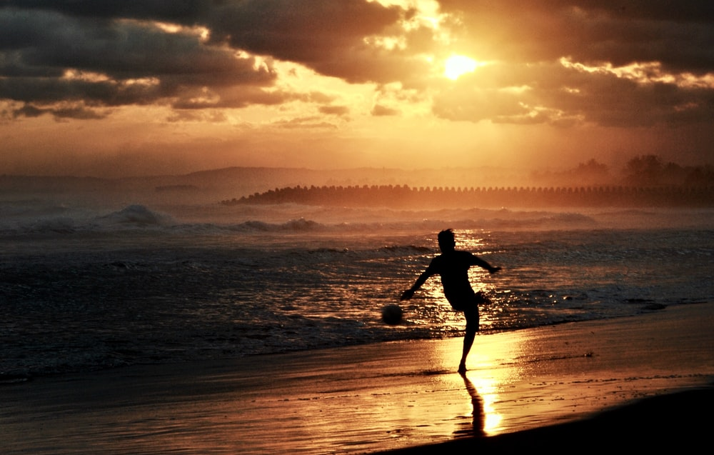 man in black shirt and shorts running on beach during sunset