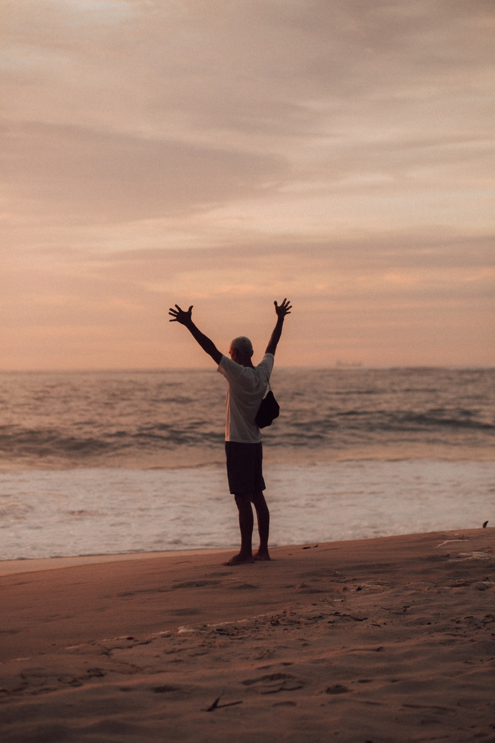 man in white shirt and black shorts standing on seashore during sunset