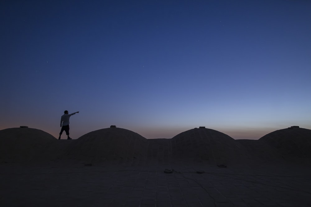 silhouette of person jumping on desert during daytime