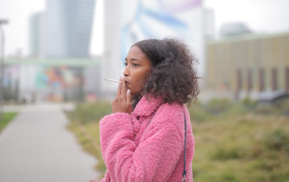 woman in pink sweater holding her chin