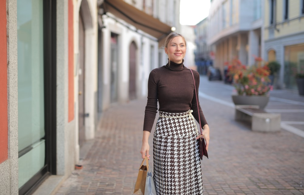 woman in black long sleeve shirt and black and white polka dot skirt standing on sidewalk