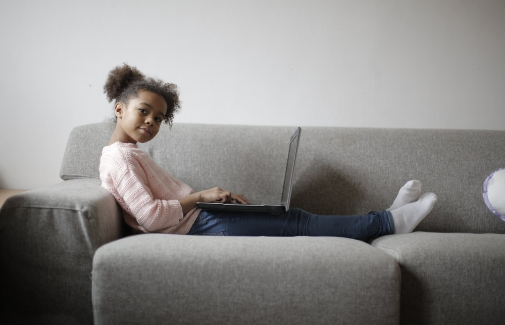 girl in pink long sleeve shirt and black pants sitting on gray couch