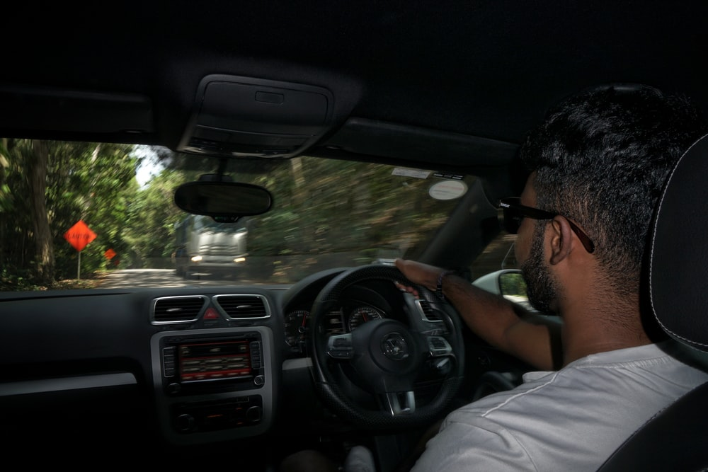 man in white shirt driving car