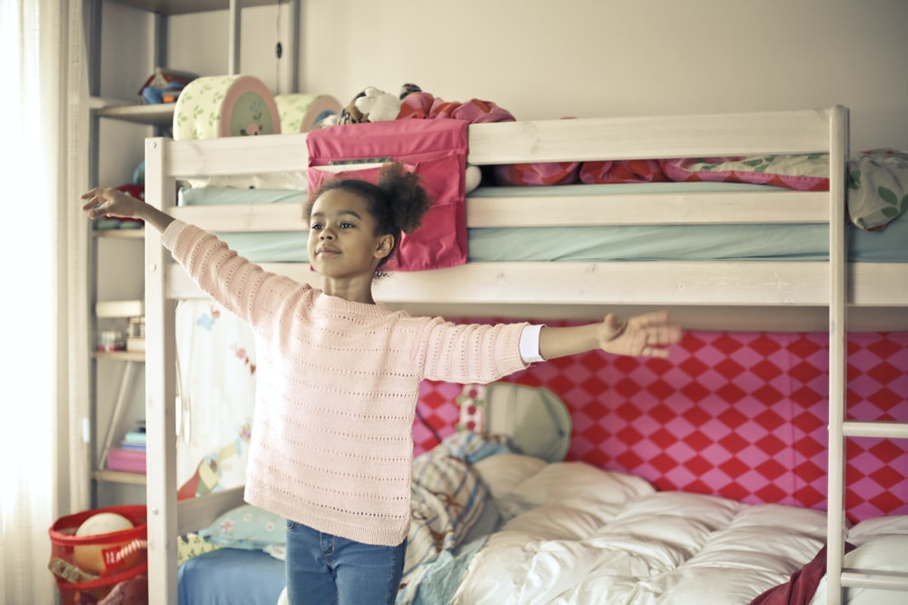 girl in white and red long sleeve shirt and blue denim jeans standing near bed