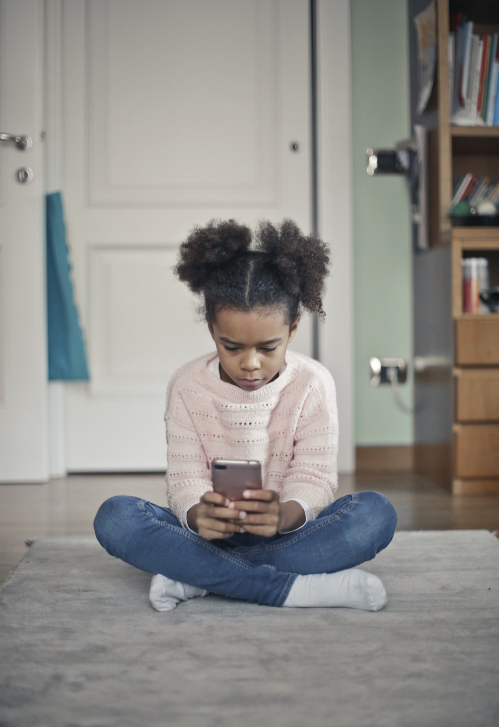 girl in white sweater and blue denim jeans sitting on floor