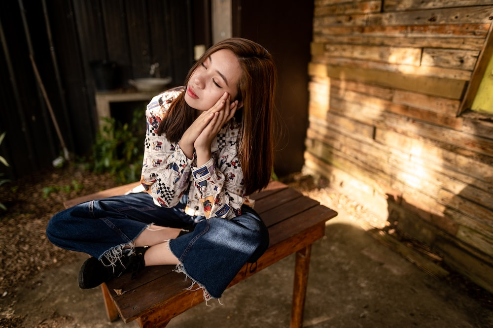woman in white and black floral long sleeve shirt and blue denim jeans sitting on brown