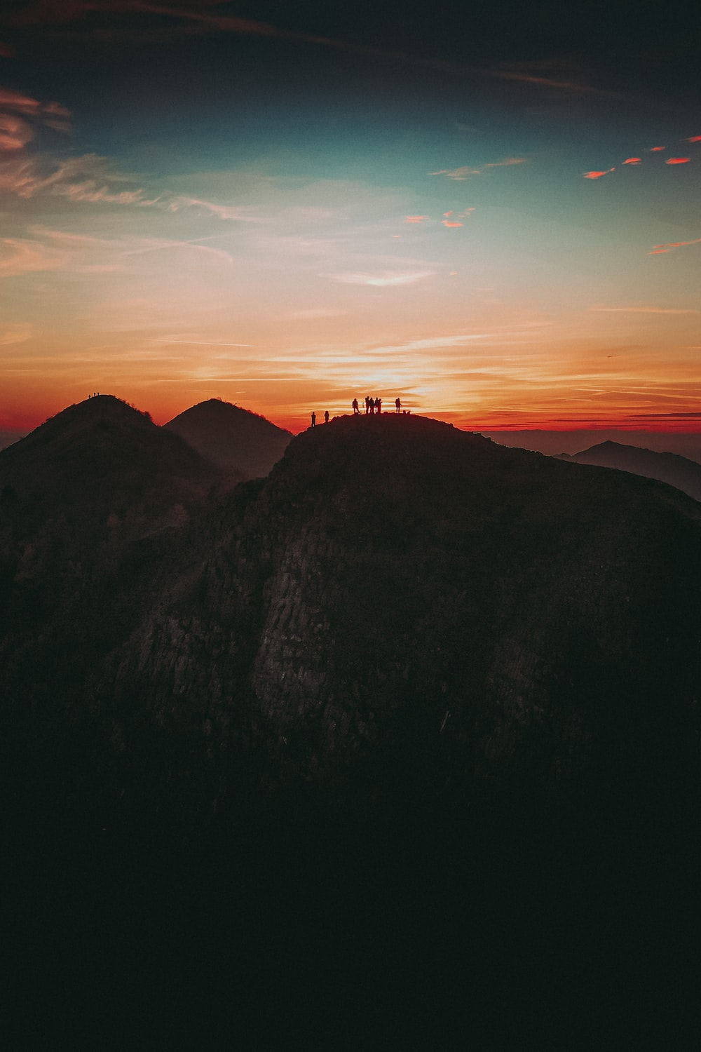 silhouette of people on top of mountain during sunset