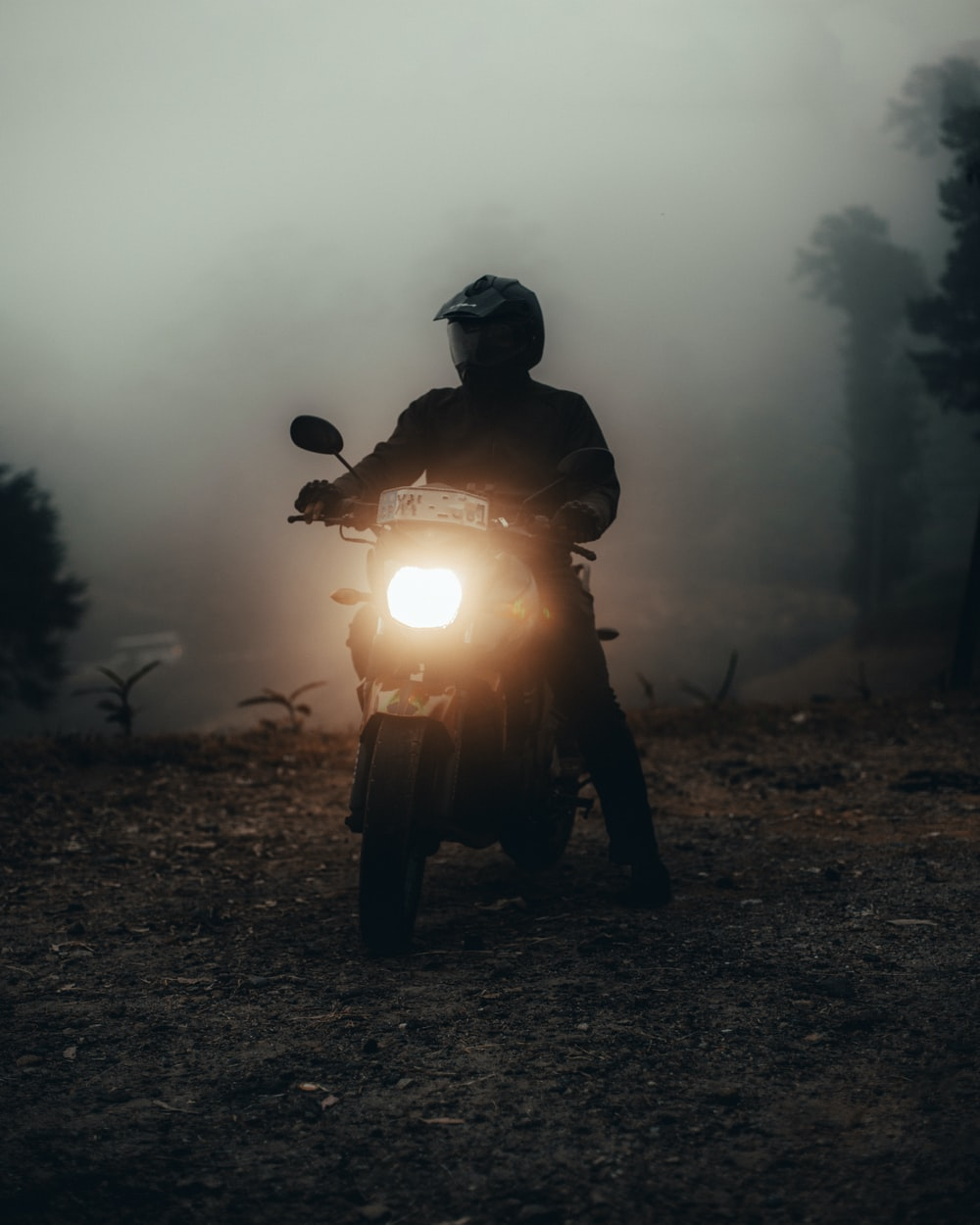 silhouette of man standing near motorcycle during night time