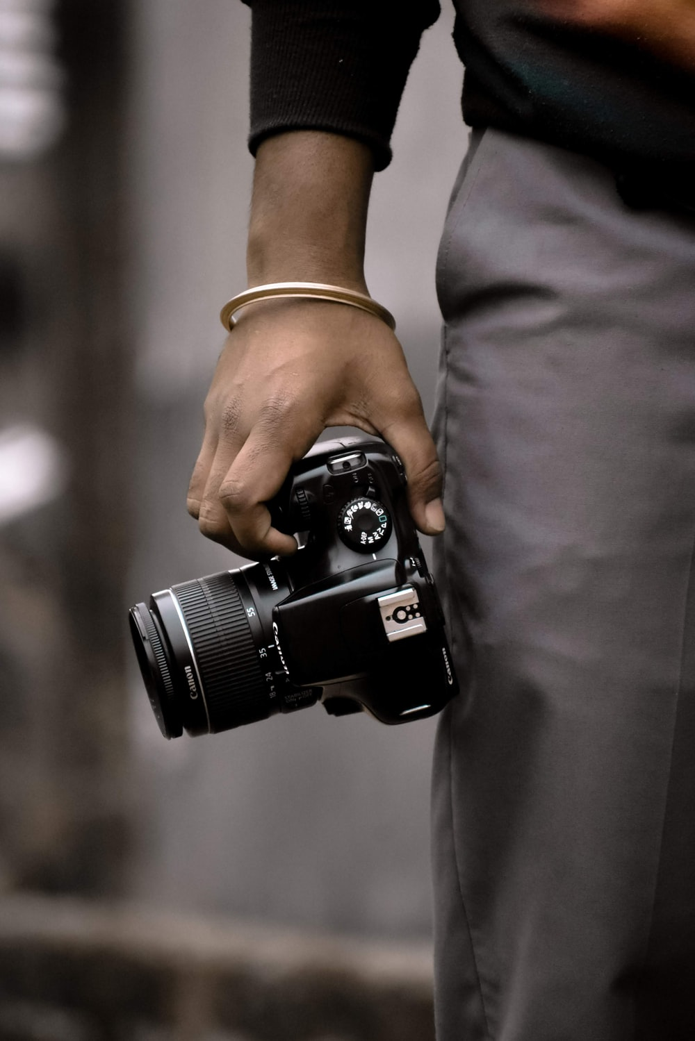 person in gray pants holding black dslr camera