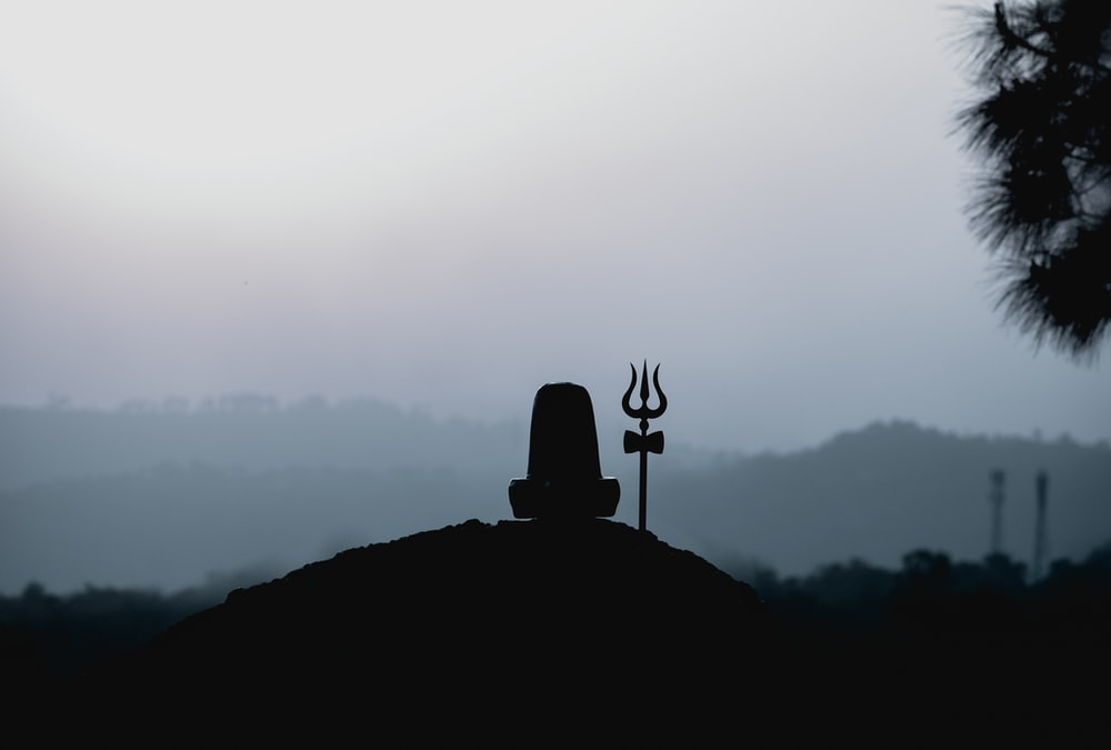 silhouette of man standing on top of mountain during daytime