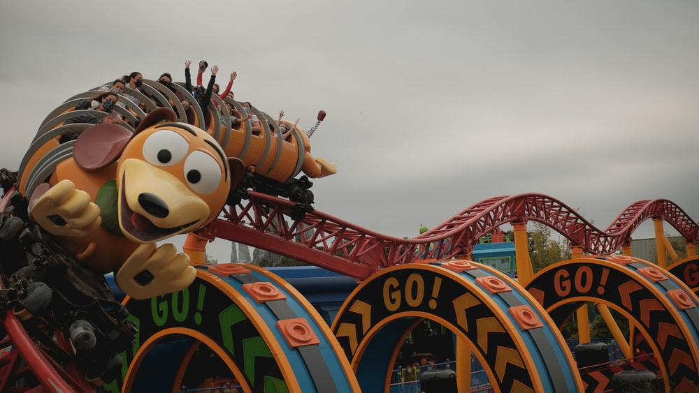 mickey mouse riding on red and blue roller coaster
