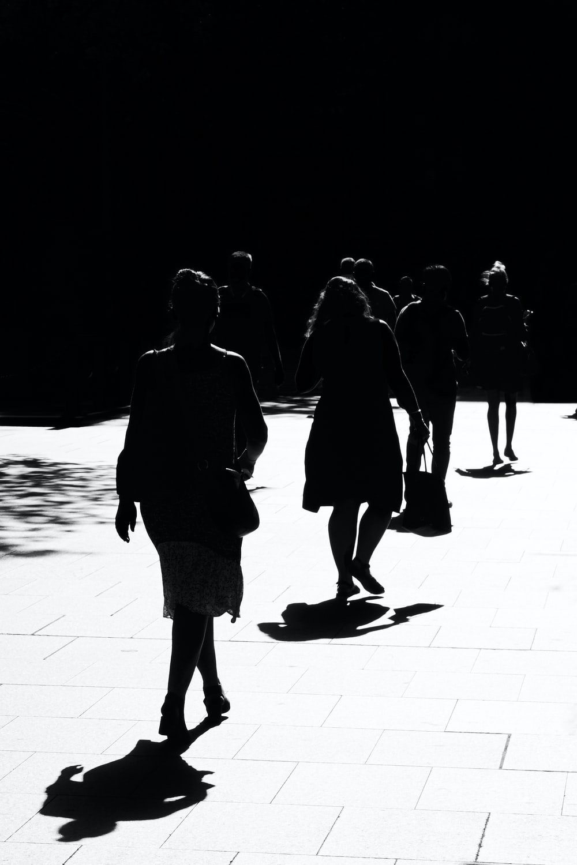 silhouette of people walking on sidewalk during night time