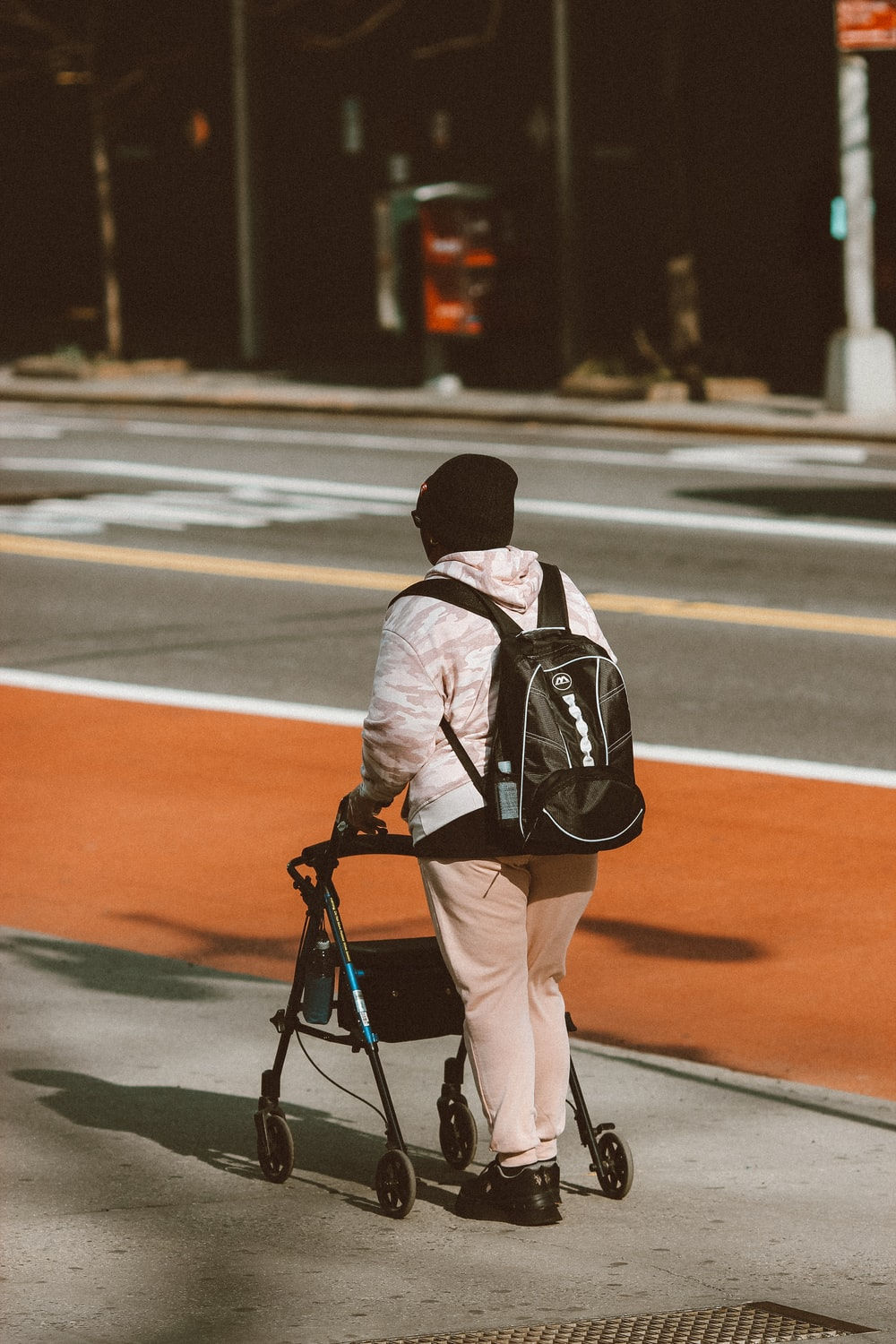 man in black and white jacket and brown pants with black backpack walking on road during