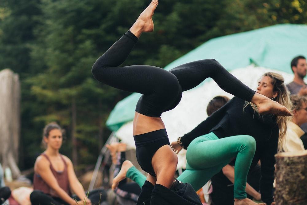 woman in black leggings and black sports bra doing yoga during daytime
