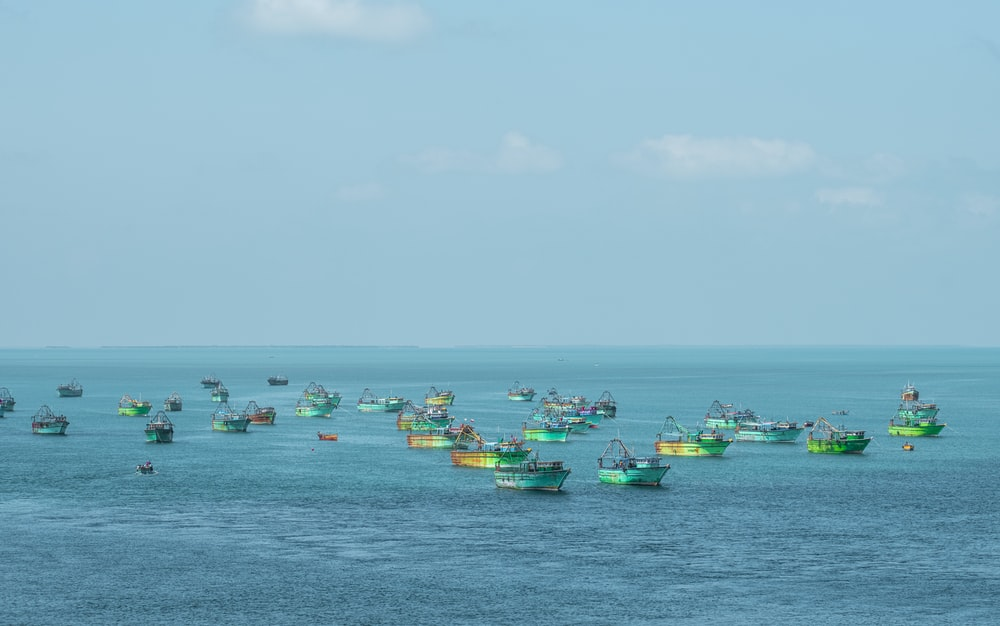 green and yellow boats on sea under blue sky during daytime