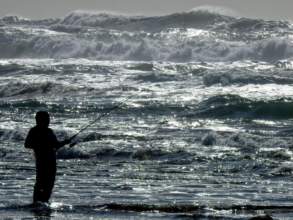 man fishing on sea waves during daytime