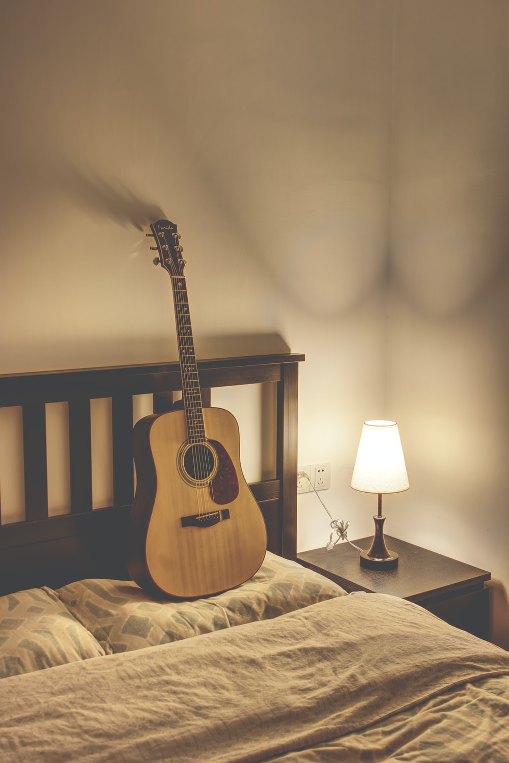 brown acoustic guitar on black stand