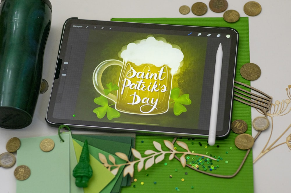 black tablet computer on green and brown textile