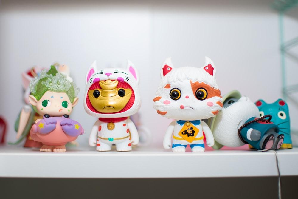 three white and red ceramic owl figurines
