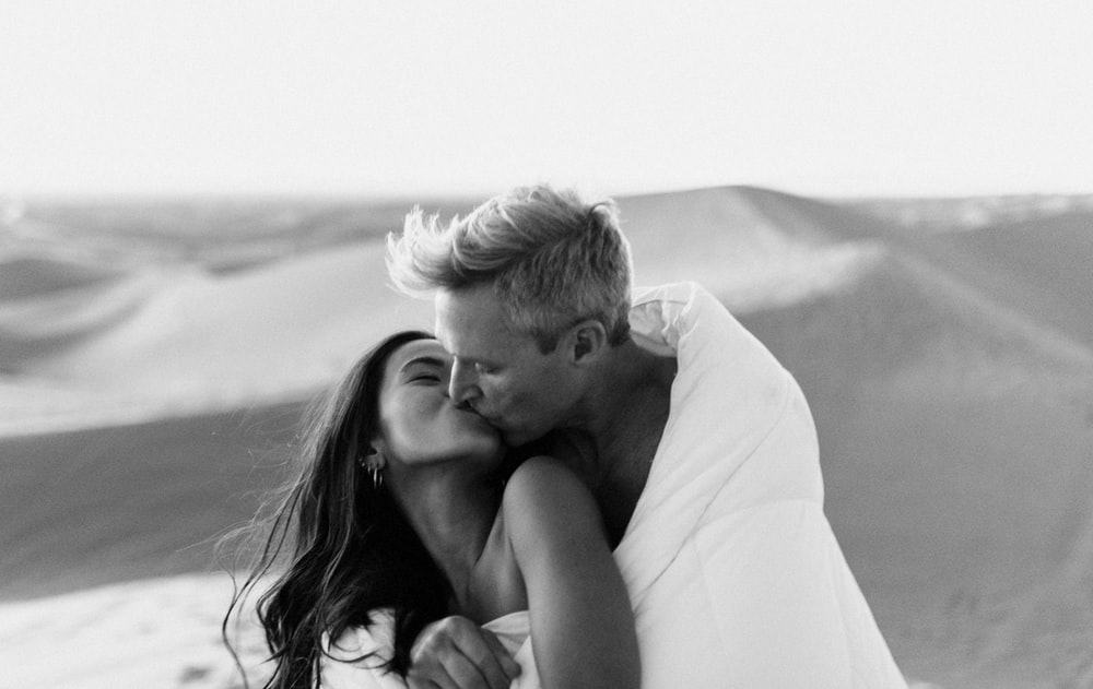 grayscale photo of man kissing woman on her cheek