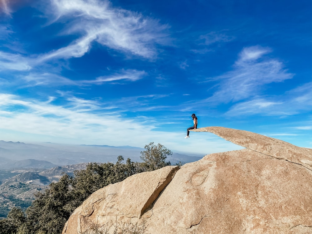 person standing on brown rock under blue sky during daytime
