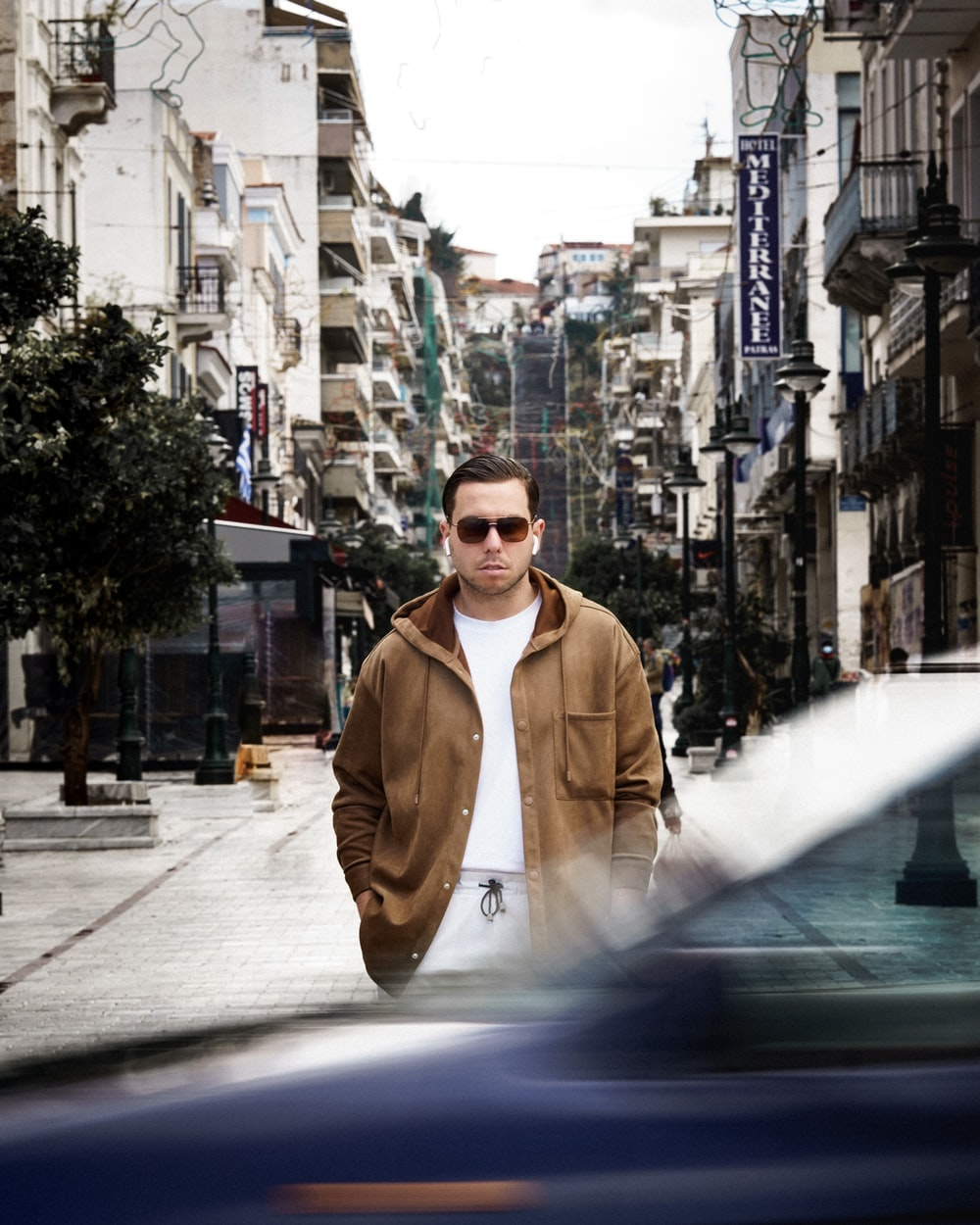 man in brown coat standing on sidewalk during daytime