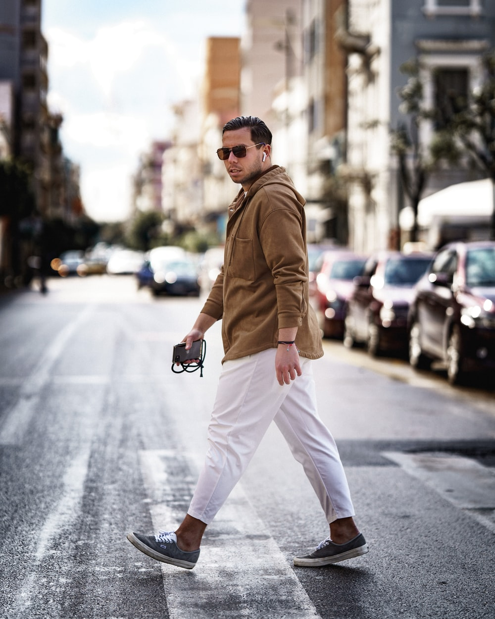 man in brown coat and white pants sitting on road during daytime