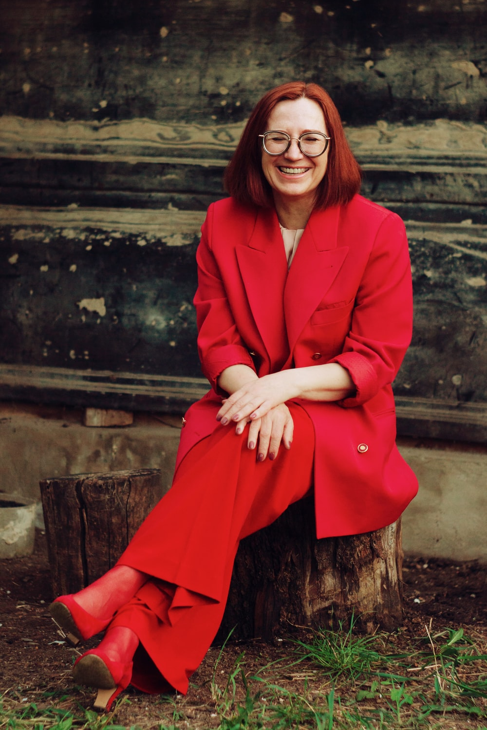 woman in red blazer and black skirt sitting on brown concrete stairs
