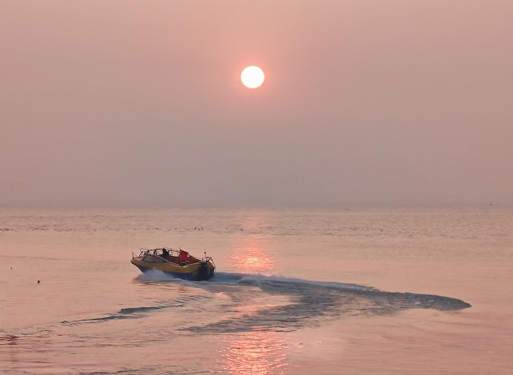man riding on orange and white boat on sea during sunset