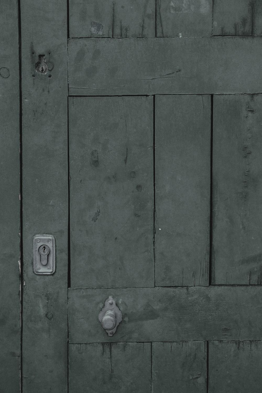 green wooden door with gray steel door knob