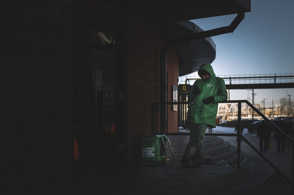 man in green jacket and green pants standing near brown building during nighttime