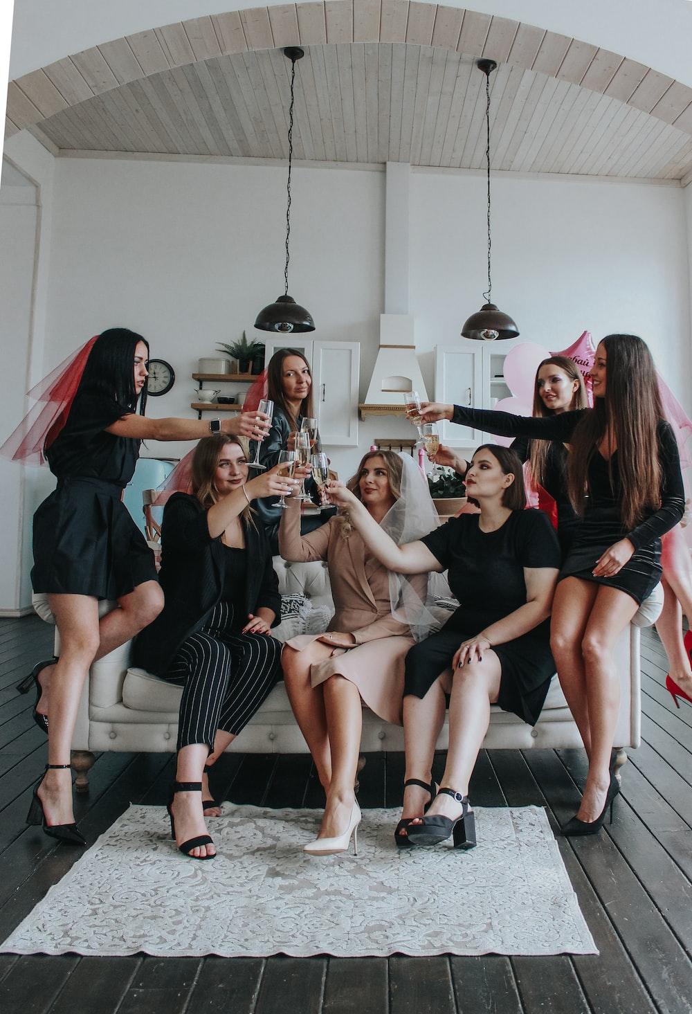 group of women sitting on white floor