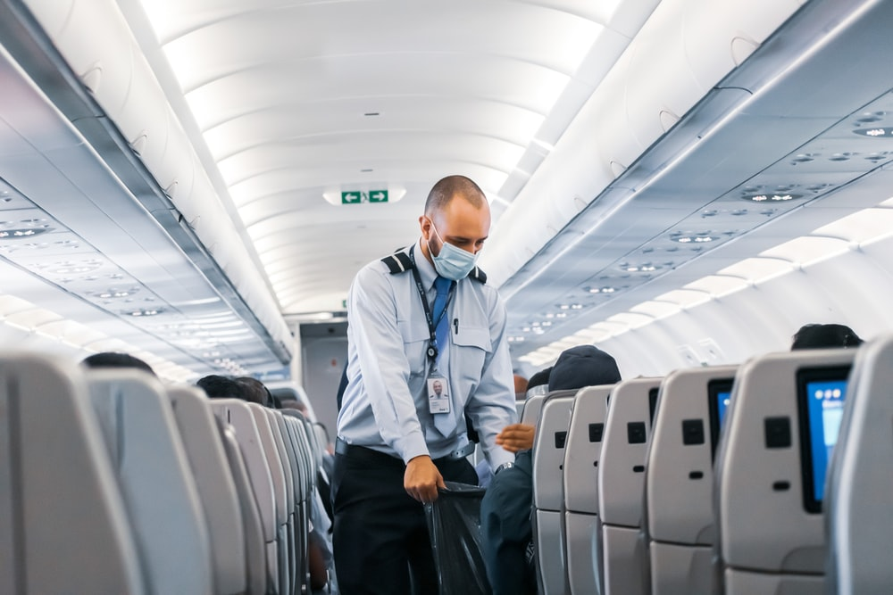 man in blue dress shirt standing in airplane