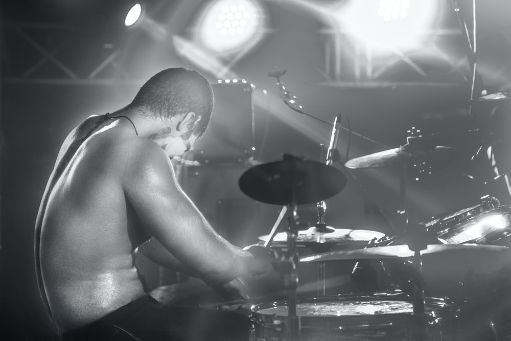 topless man playing drum set