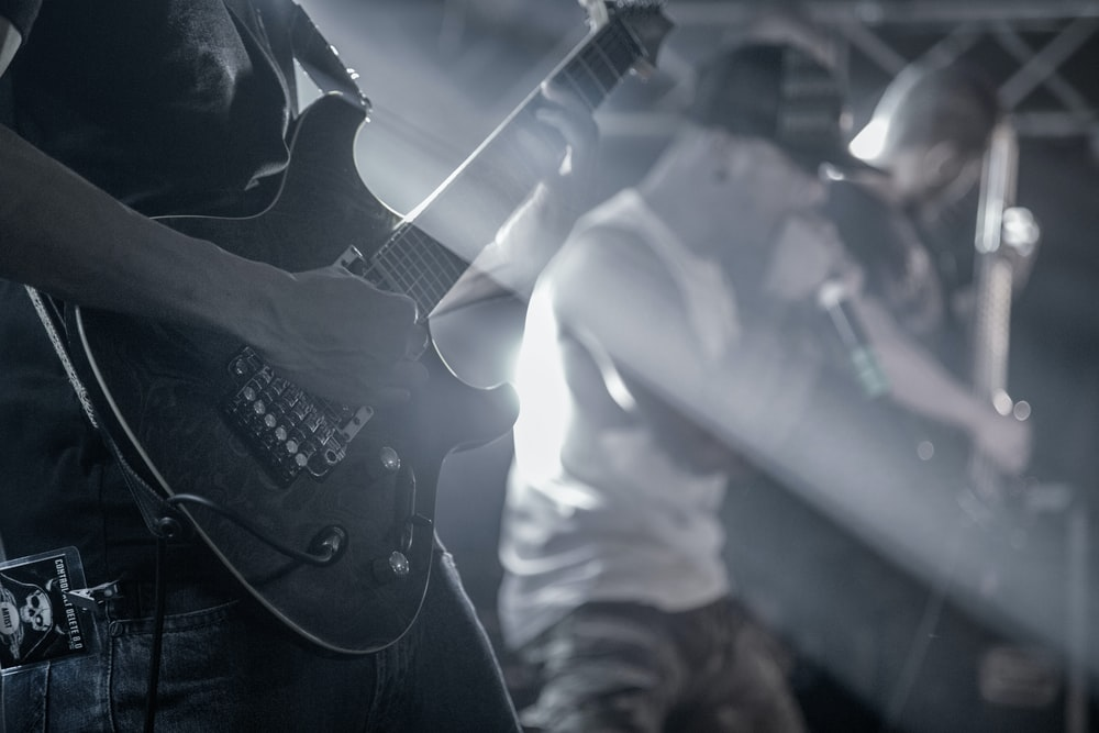 man playing electric guitar in grayscale photography
