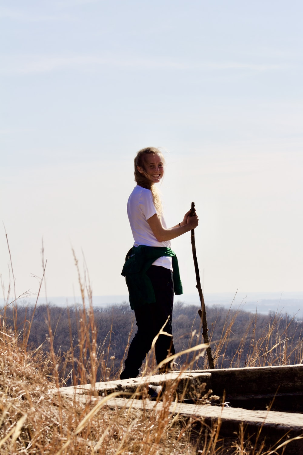 woman in white shirt and black pants holding stick standing on brown grass field during daytime