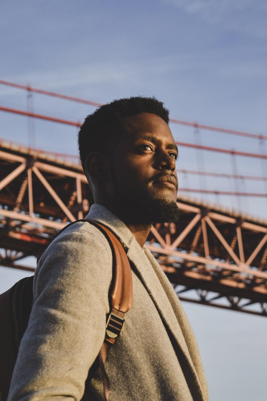 man in gray shirt standing near bridge during daytime