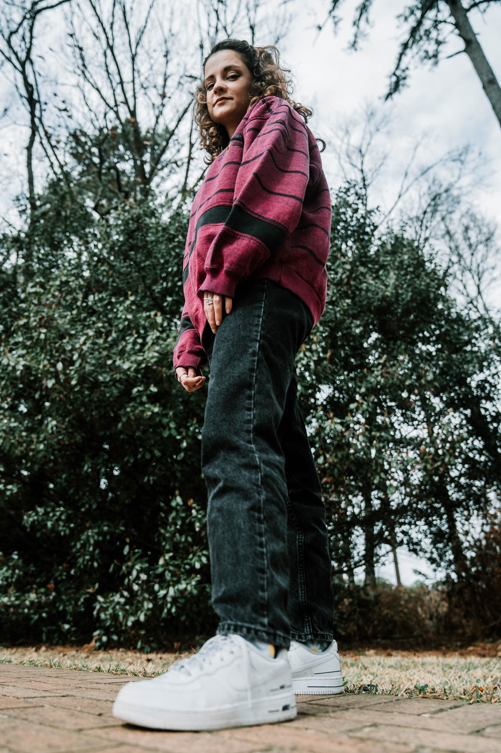 man in red and black jacket and blue denim jeans standing near green trees during daytime
