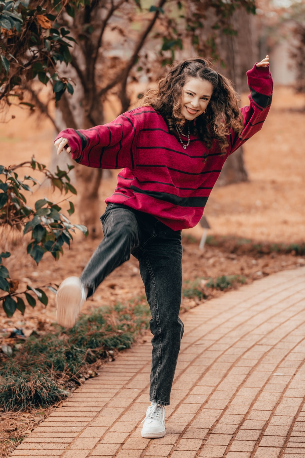 woman in red long sleeve shirt and blue denim jeans jumping on brown brick pathway during