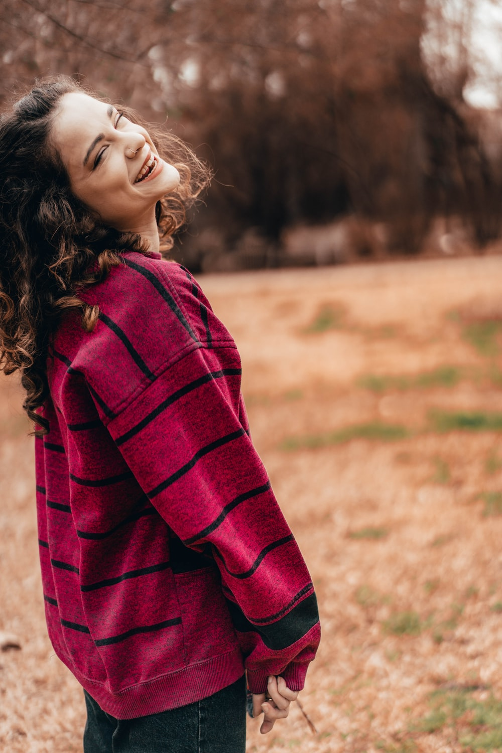 woman in red and black checkered long sleeve shirt standing on green grass field during daytime