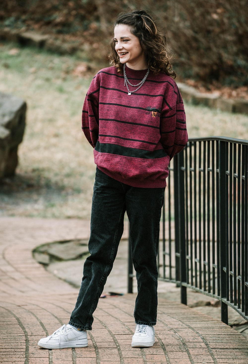 woman in pink and black striped hoodie standing near black metal fence during daytime