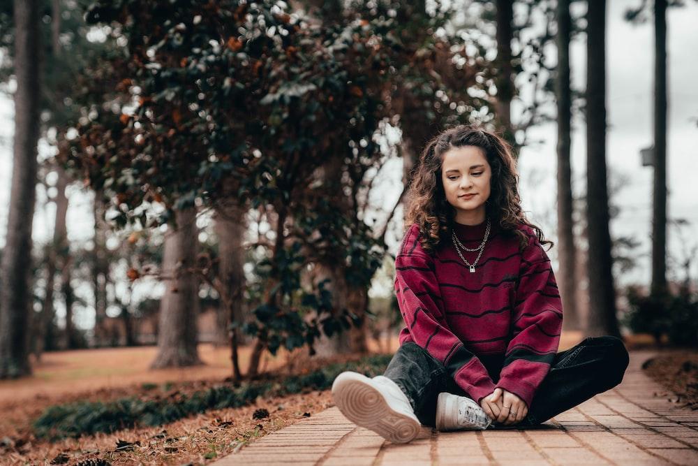 woman in purple hoodie sitting on brown wooden bench
