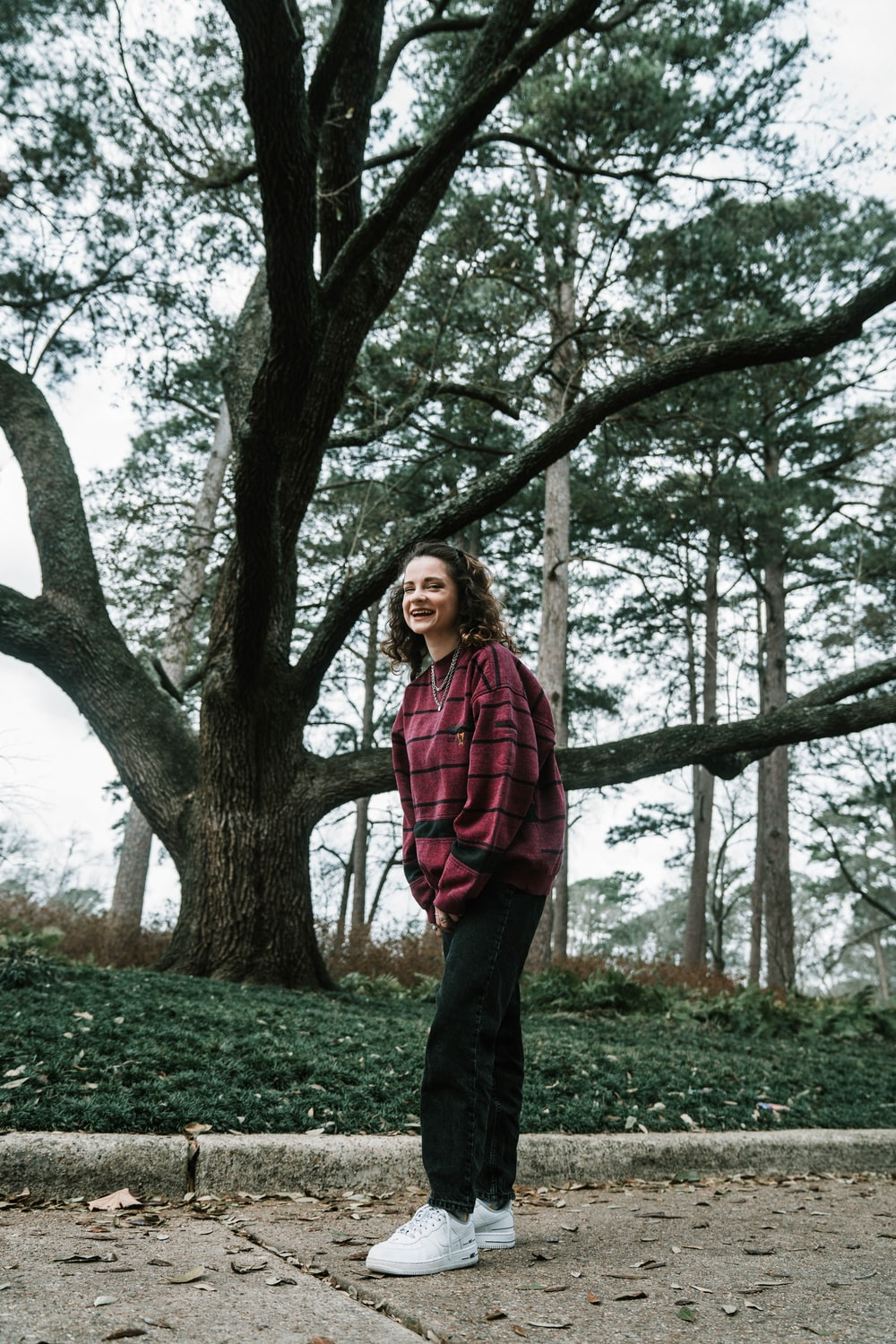 woman in red and black plaid dress shirt standing near brown tree during daytime