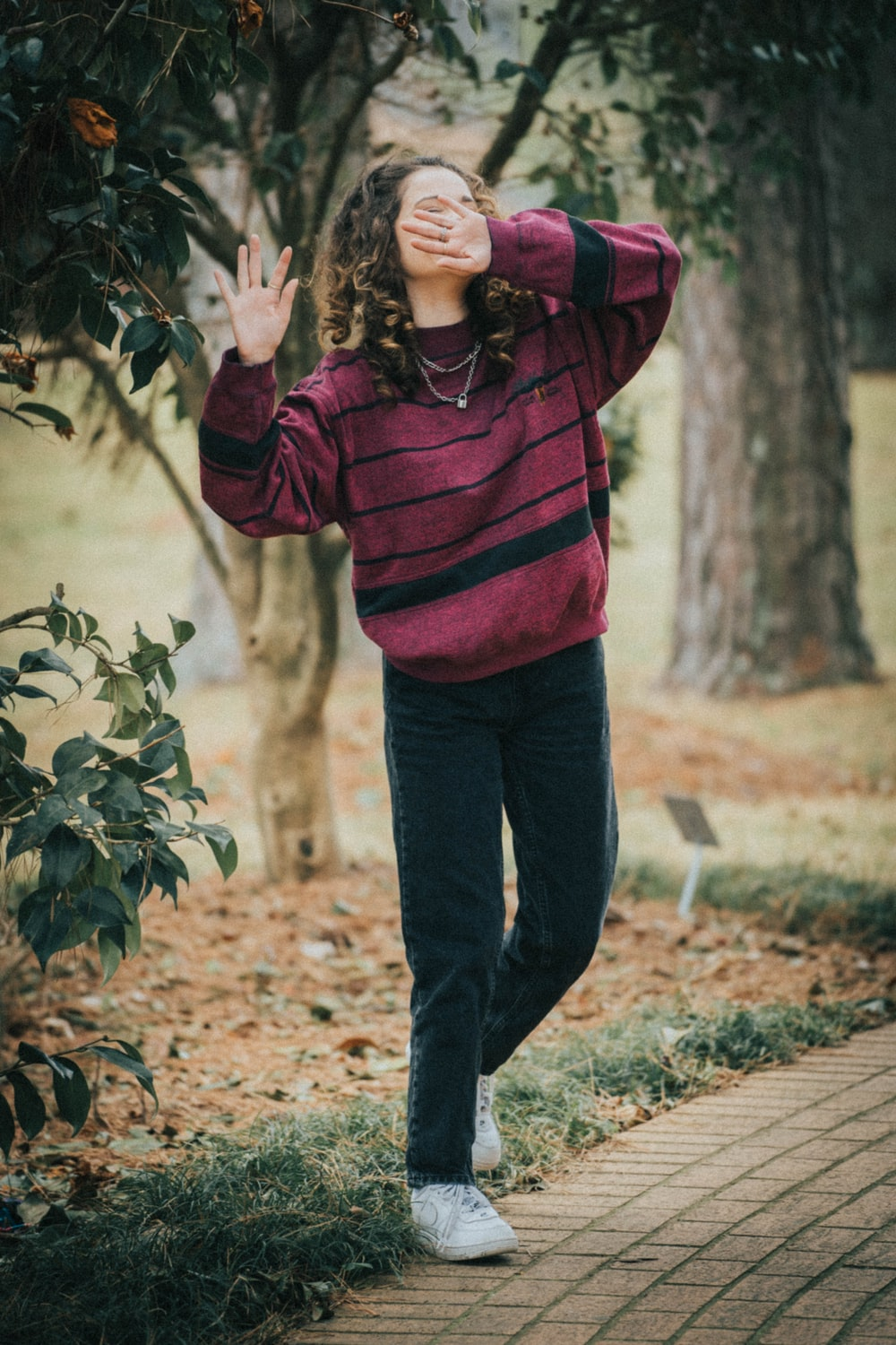 woman in red and black striped hoodie standing on brown dried leaves during daytime