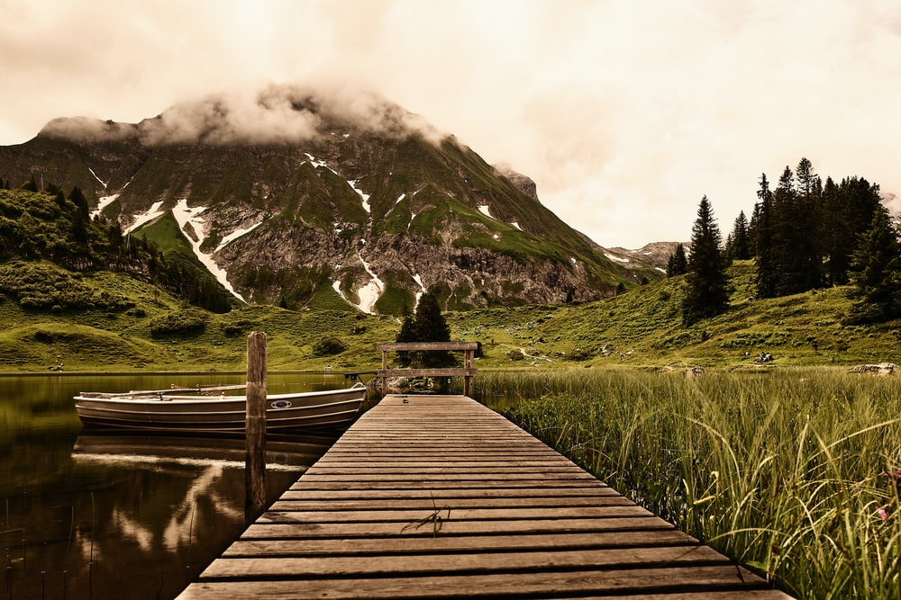 brown wooden dock on green grass field near mountain during daytime